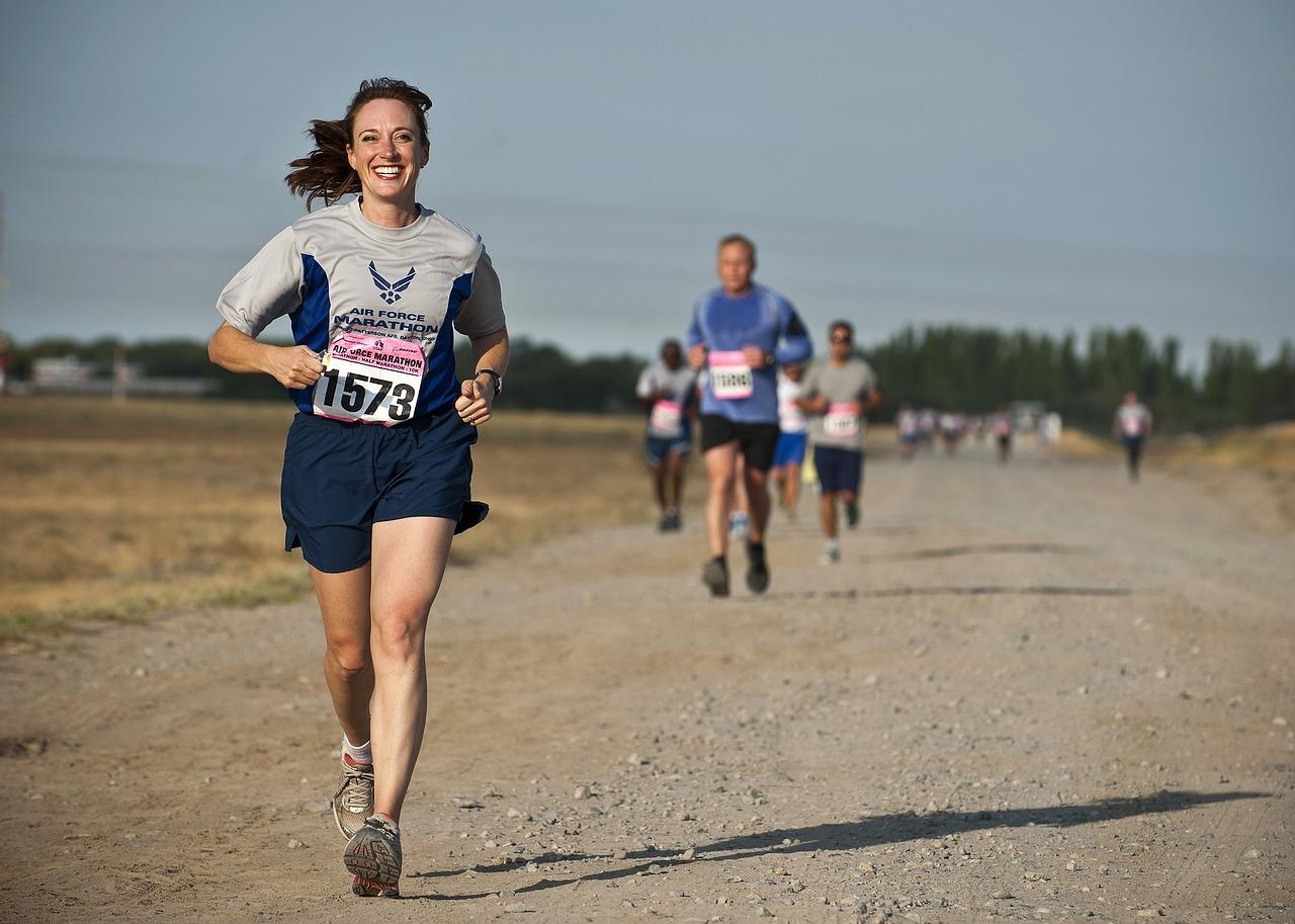 Femme en train de courir avec le sourire pendant une compétition